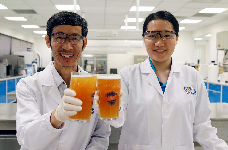 A Szingapúri Állami Egyetem kutatói, Alcine Chan és Liu Shao Quan az általuk kifejlesztett, probiotikus sörrel. (Fotó: Reuters/Edgar Su)